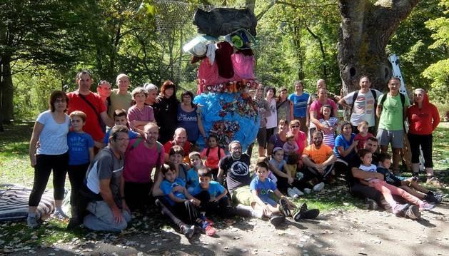 Foto de los participantes en la limpieza del río posan tras la jornada junto a la escultura realizada con los desperdicios retirados.