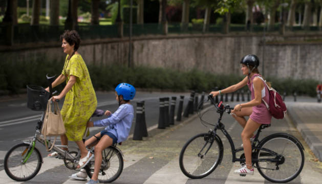 Varias personas cruzan un paso de peatones en bici en Pamplona.
