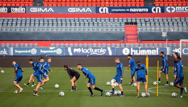 Los jugadores de Osasuna realizan ejercicios de calentamiento en el inicio de la sesión a puerta cerrada que tuvo lugar ayer en El Sadar.