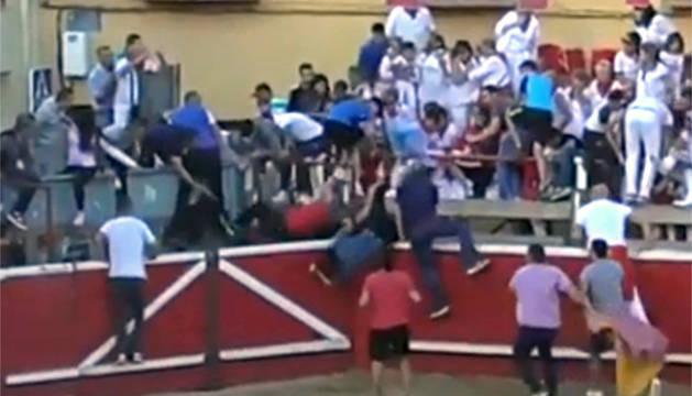 El herido más grave, con camiseta roja en el callejón, es volteado por el toro tras saltar el vallado.