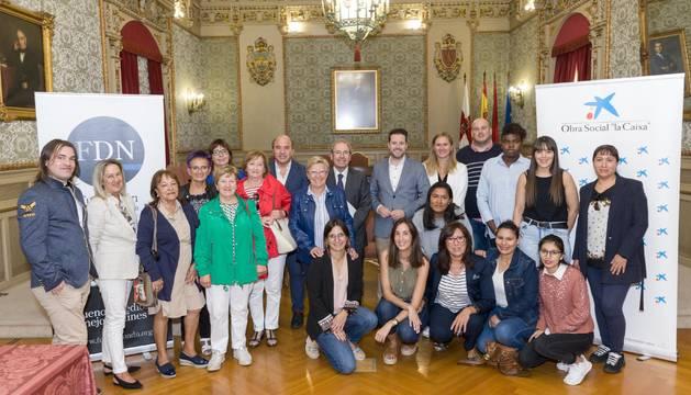 Representantes de las entidades promotoras del Reto Solidario y de las entidades sociales de Muévete por Tudela posan juntos en el salón de plenos del Ayuntamiento.