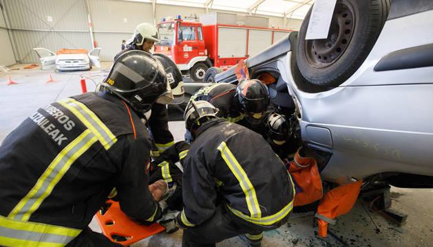 Foto de un grupo de bomberos realizando un ejercicio para practicar la excarcelación de una víctima de accidente de tráfico.