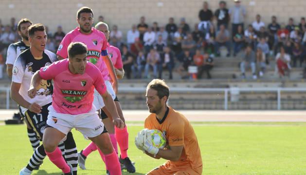 Foto del portero del Tudelano Mikel Pagola captura el balón protegido por Diego Royo.