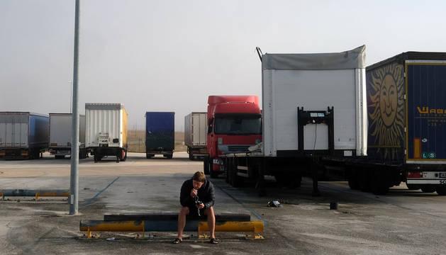 Uno de los camioneros espera en explanada de la Ciudad del Transporte. Al fondo, varios camiones estacionados.