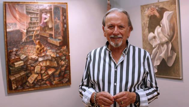 Foto del pintor valenciano Álex Alemany junto a dos obras de la exposición Imaginación y surrealismo que puede verse en Pamplona.