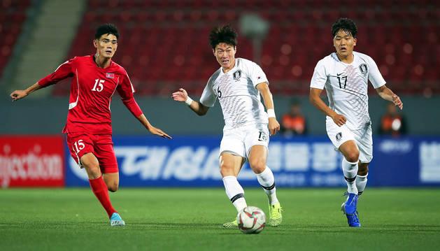 El surcoreano Hwang Ui-jo golpea el esférico en presencia del rival de Corea del Norte, Ri Un-chol.