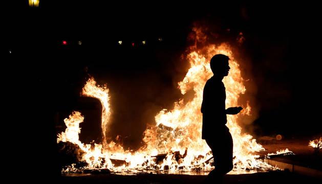 Foto de un manifestante camina junto a uno de los fuegos provocados en las calles de Barcelona.