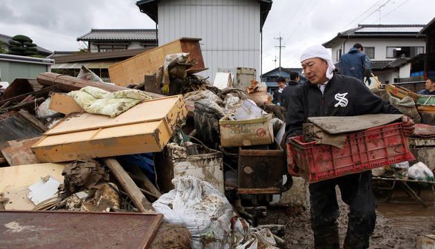 Un hombre transporta enseres afectados por las inundaciones en Nagano.