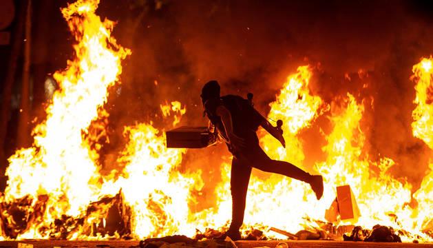 Un manifestante echa al fuego un cartón junto a la Delegación del Gobierno en Barcelona.