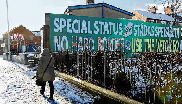 Una persona pasea junto a una valla publicitaria que pide un estatus especial para Irlanda del Norte con respecto al Brexit, en Belfast.
