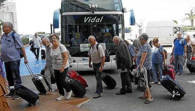 Un grupo de jubilados llega en autobús hasta la entrada de un establecimiento hotelero.