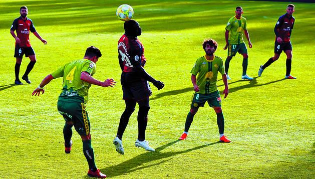 El jugador de Osasuna Promesas Marcos Mendes peina el balón entre los futbolistas de Unionistas Zubiri y Javi Navas, durante el partido de ayer en Tajonar.