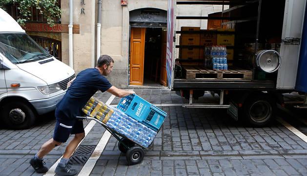 Foto de Óscar Ballaz, en plenas labores de descarga de bebidas en la calle Curia.