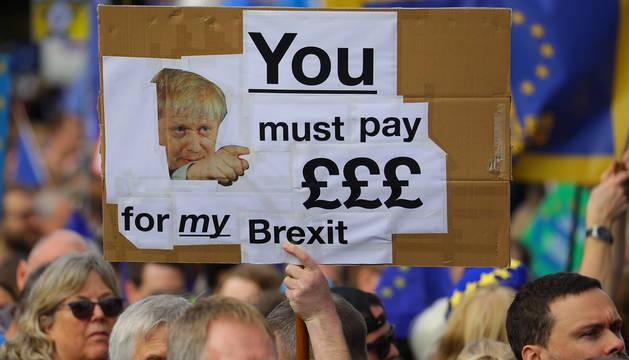 Un manifestante contrario al Brexit sostiene una pancarta contra Boris Johnson.