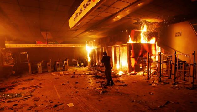 Una persona se cubre del humo y de las llamas en una estación del metro de Santiago incendiada.