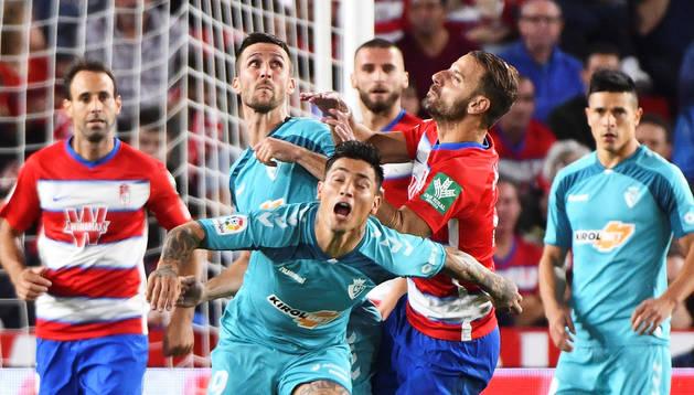 Facundo Roncaglia, a la derecha detrás, observa la pugna de su compañero 'Chimy' Ávila con los rivales del Granada.