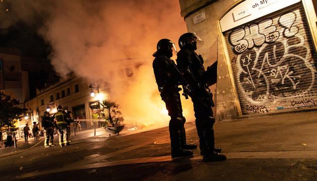 Mossos d'esquadra controlan una calle de el raval mientras los bomberos apagan una barricada de fuego.