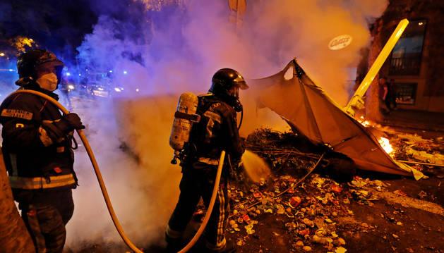 Foto de bomberos sofocan una barricada este sábado en Barcelona.