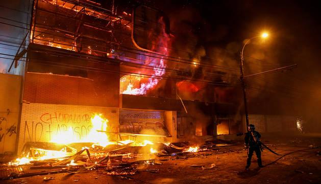 Un bombero lucha contras las llamas en un supermercado incendiado en Valparaiso.