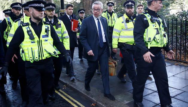 Michael Gove es escoltado en su camino al Parlamento inglés.