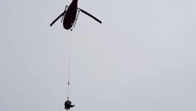 Foto de David Suela, colgado con una sirga del helicóptero en su rescate.