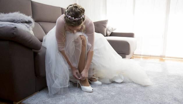 Una novia se abrocha el zapato que han creado para ella en Calzados Marpe.
