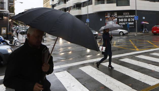 Paraguas para frenar la lluvia este martes, 22 de octubre, por las calles de Pamplona.