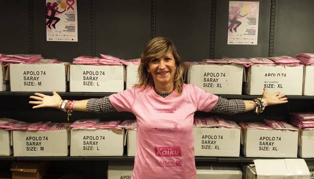 Izaskun Echechipia, de Saray, muestra las camisetas disponibles en el punto de venta de dorsales de la asociación en la quinta planta de El Corte Inglés de Pamplona