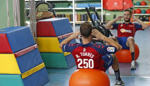 Roberto Torres realiza un ejercicio apoyado en una pelota frente al espejo, este miércoles en el gimnasio de Tajonar, mientras luce la camiseta de Osasuna con el 250, su número de partidos como rojillo.
