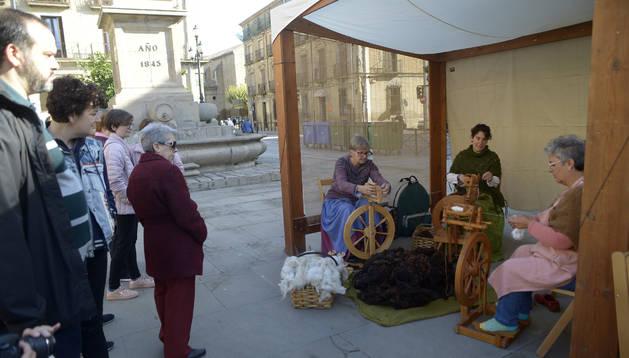 Mia Rissanen, Amelia Torres y Arantxa Díez muestran al público el oficio de hilar lana durante las ferias de Tafalla.