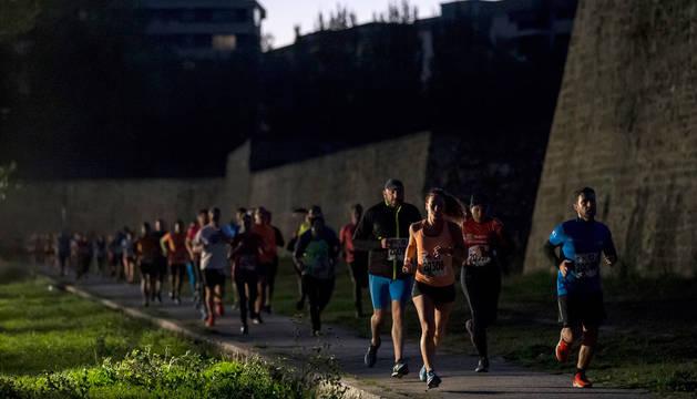 foto de Un grupo de participantes, a la carrera por los fosos de la Ciudadela de Pamplona