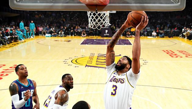 Anthony Davis, de los Lakers, entra a canasta entre dos rivales de los Hornets de Charlotte.