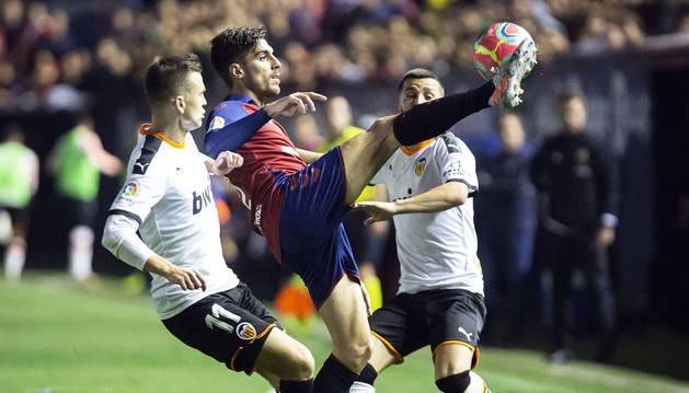 Nacho Vidal despeja el esférico en un momento del encuentro contra el Valencia en presencia de dos rivales