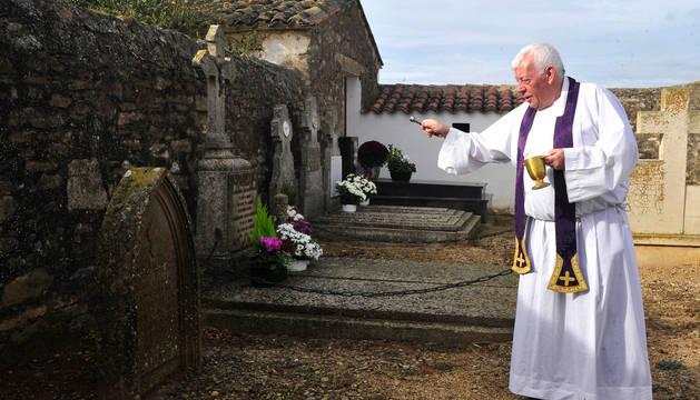 Foto del padre Nacho bendiciendo una de las tumbas más antiguas en Traibuenas.