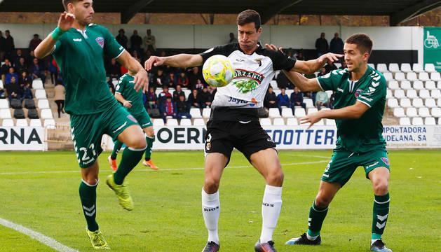 El delantero del Tudelano, Koldo Obieta 'Obi', entre dos rivales, marcó el gol que le dio el triunfo ayer a su equipo.