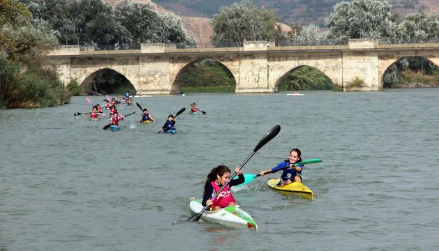 foto de Varios jóvenes navegan con piraguas por el río Ebro con el puente de Tudela a sus espaldas.