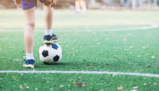 Un menor, de espaldas, controla el balón sobre el terreno de juego.