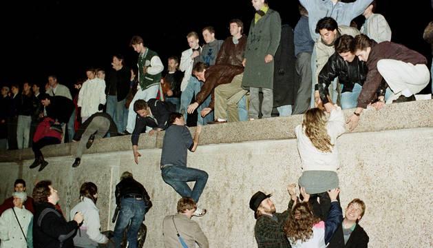 Alemanes del Este escalan el Muro de Berlín el 10 de noviembre de 1989.