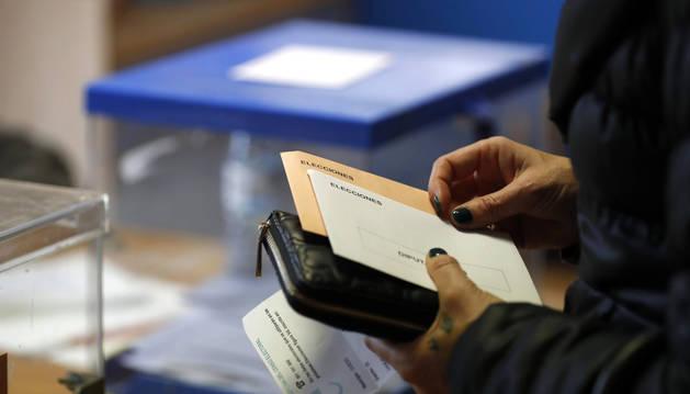 foto de Una mujer espera su turno ante la urna para poder votar