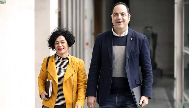 Los socialistas Inma Jurío y Ramón Alzórriz caminan por un pasillo del Parlamento.