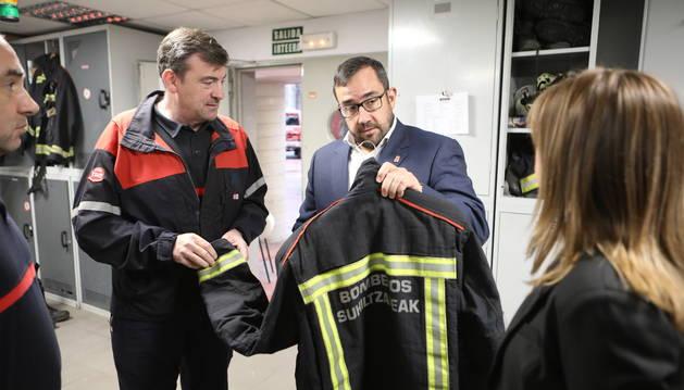 El consejero Remírez observa uno de los trajes de bomberos junto a Baldanta.