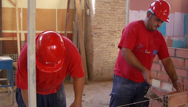 Dos alumnos realizan trabajos de albañilería durante uno de los cursos que organiza la Fundación Laboral de la Construcción.