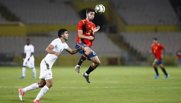 Ferran Torres cabecea el balón en presencia de un rival de Israel.
