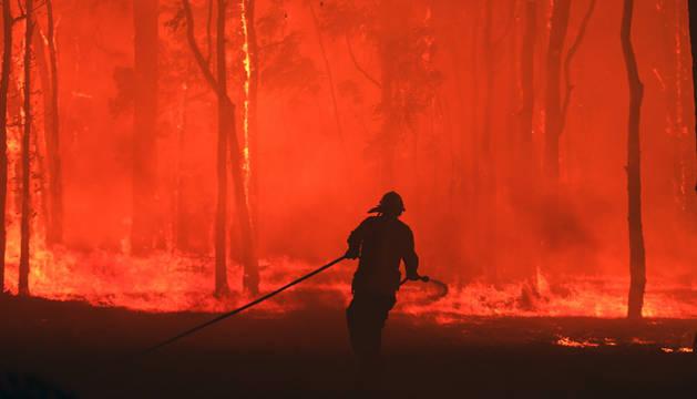 Un bombero de Nueva Gales del Sur lanza agua contra las llamas que alcanzan una casa en Gosper Mountains, al suroeste de Sídney (Australia).
