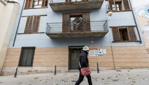 Foto de una mujer camina frente a la fachada de la sede de Eder, donde este sábado se celebrará la asamblea.