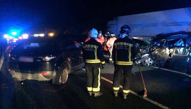 Bomberos de Navarra realizar las labores de limpieza de la calzada junto a los dos vehículos implicados en la colisión frontal.