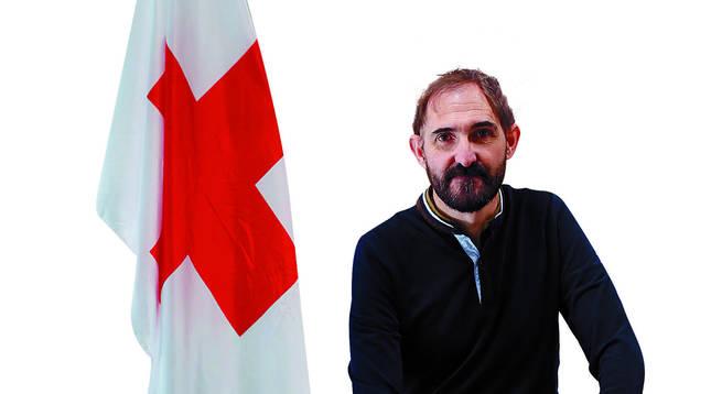 Rafael Huarte posa con la bandera de la Cruz Roja y un maletín original de los que utilizaban los pioneros de la entidad, restaurado. Ambos adornan su despacho, en la tercera planta de la sede, en la calle Leyre.