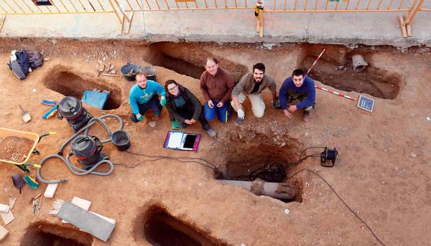Foto de parte del equipo de arqueólogos que ha trabajado en la necrópolis islámica de Ribaforada, junto a varias de las fosas excavadas.