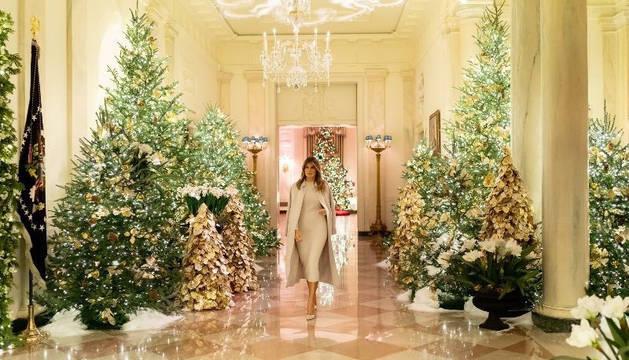 Melania Trump camina por el Cross Hall de la Casa Blanca donde ha 'plantado' varios pinos naturales adornados con nieve artificial y dorados.