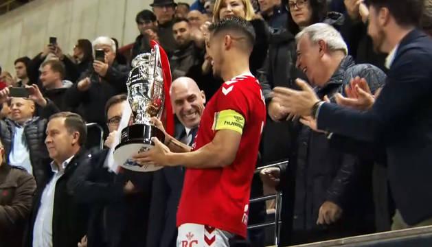 Armando, capitán del Murcia, levanta el trofeo que acredita a los pimentoneros como campeones.